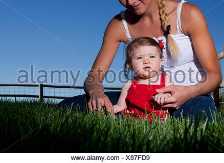 Portrait of mid adult woman sitting on grass with toddler daughter - Stock Photo