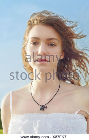 Portrait of serene young woman with hair blowing in breeze - Stock Photo