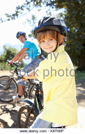 Little boy on country bike ride with dad - Stock Photo