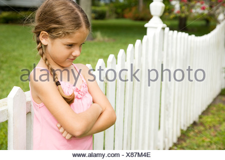 little girl standing against fence with arms folded - Stock Photo