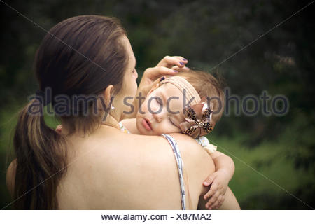 Close-Up Rear View Of A Mother Carrying Baby Outdoors - Stock Photo