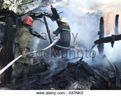 firefighters extinguish a fire in an apartment house - Stock Photo