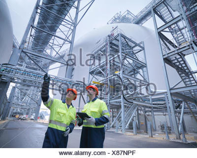 Workers in discussion in biomass facility, low angle view - Stock Photo