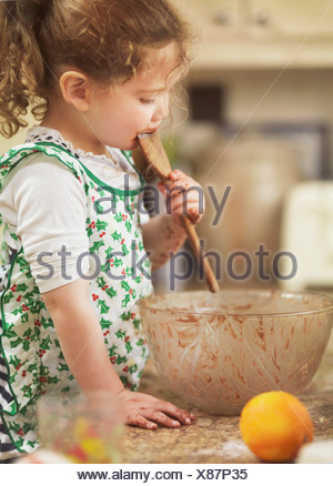 Child tasting cake mix with wooden spoon - Stock Photo