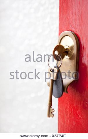 Close up of house keys in front door - Stock Photo