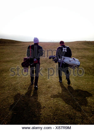 Rear view of two golfers walking on a golf course, Scotland, UK - Stock Photo