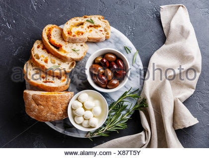 Olives, mini Mozzarella cheese and sliced Ciabatta bread with cheese on dark background - Stock Photo