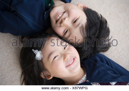 Portrait of brother and sister lying on carpet - Stock Photo
