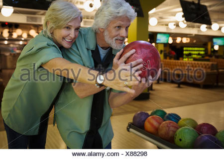 Wife guiding husband bowling at bowling alley - Stock Photo