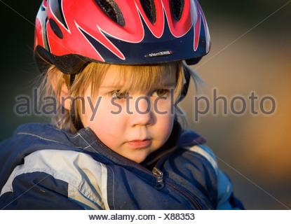 Girl, 4, wearing a bicycle helmet, portrait - Stock Photo