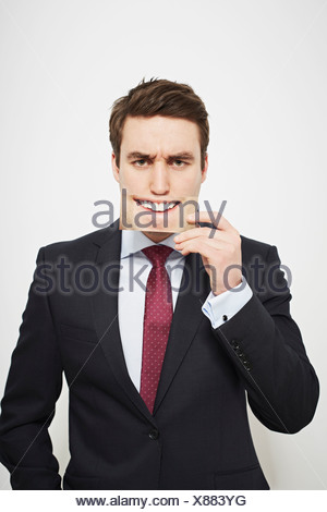 Businessman holding angry picture over his face - Stock Photo