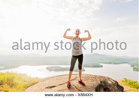 Young woman standing on top of mountain and flexing muscles - Stock Photo
