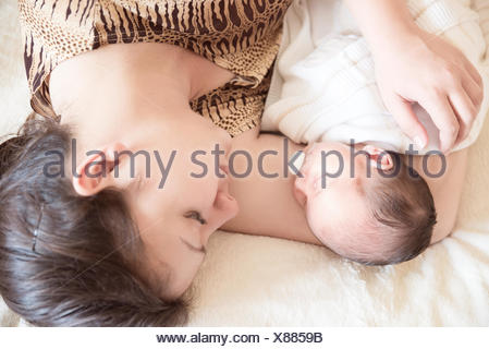 Mother lying on bed with newborn baby boy - Stock Photo