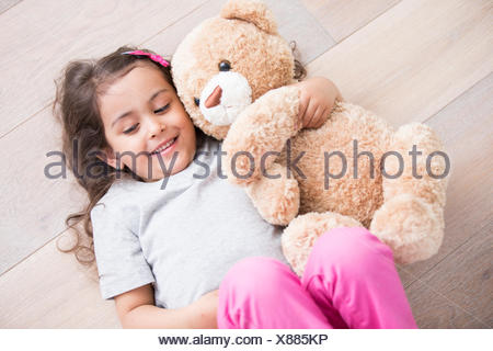 Girl with teddy bear lying on wooden floor at home - Stock Photo