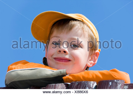 Portrait of a boy, six years of age, wearing a baseball cap - Stock Photo