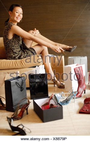 Woman putting on high heel shoes, surrounded by shopping bags and shoes - Stock Photo