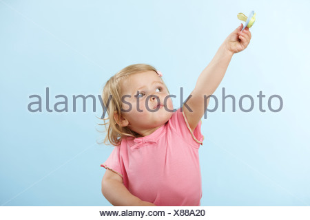 Girl holding pacifier - Stock Photo