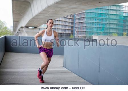 MODEL RELEASED. Young woman running in urban scene. - Stock Photo