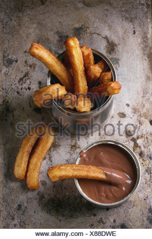 Traditional spanish treat churros with chocolate sauce, served in tin can over old textural metal background. Top view with copy - Stock Photo