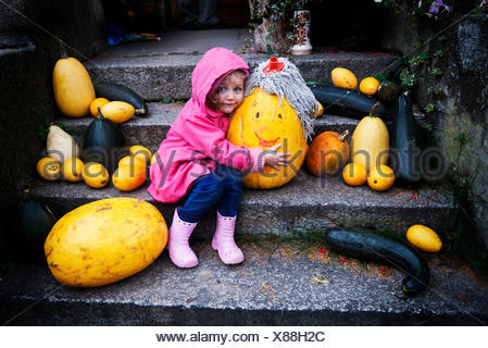 Girl (4-5) embracing pumpkin with mop on its head - Stock Photo