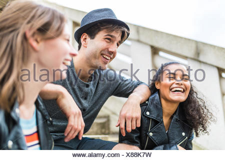 Three young adult friends on stairway chatting in Battersea Park - Stock Photo