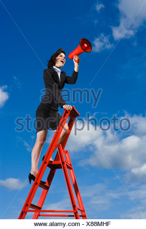 Businesswoman  standing on top of red ladder against blue sky and shouting through red megaphone - Stock Photo