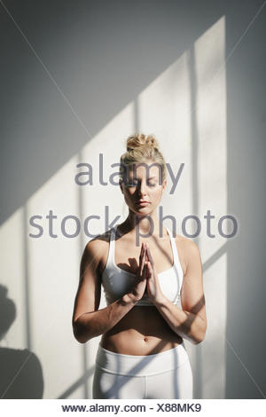 A blonde woman, her eyes closed, in a white crop top and leggings, standing in front of a white wall, doing yoga. - Stock Photo