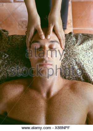 Couple at Spa in Northern Thailand: View from above of male lying on back having forehead massaged by female masseuse Brent - Stock Photo