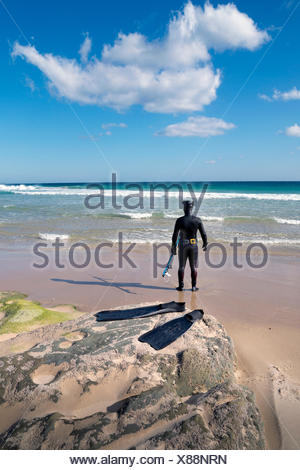 Man in wetsuit standing on beach, Los Lances, Tarifa, Cadiz, Andalucia, Spain - Stock Photo
