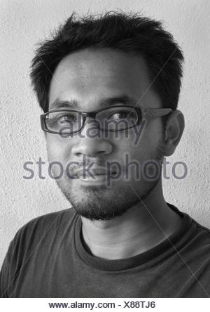 Portrait of young man wearing glasses - Stock Photo