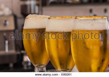 Three glasses of Fresh draught beer on bar - Stock Photo