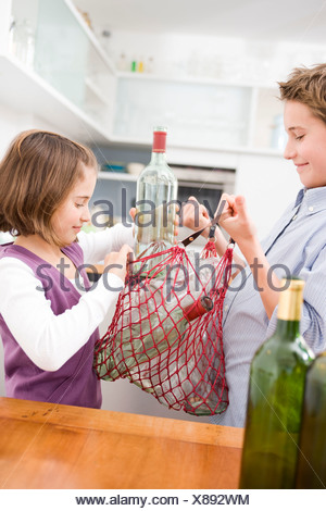 Boy and girl recycling empty bottles - Stock Photo