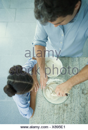 Girl watching as father mixes dough, high angle view - Stock Photo