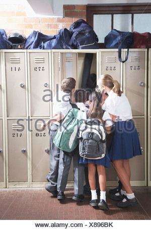 Students in the school hallway looking in a locker - Stock Photo