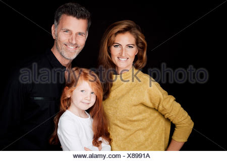 Portrait of smiling couple with little daughter in front of black background - Stock Photo