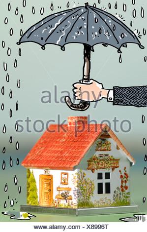Hand holding umbrella above house, close-up - Stock Photo