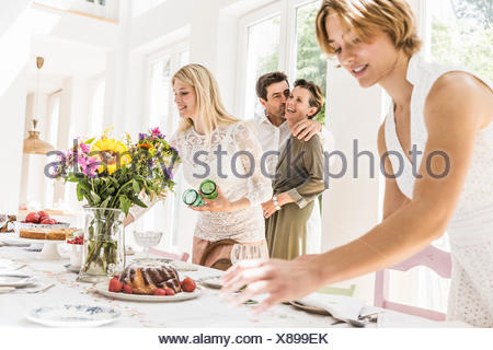 Family making preparations to dining room table for party - Stock Photo