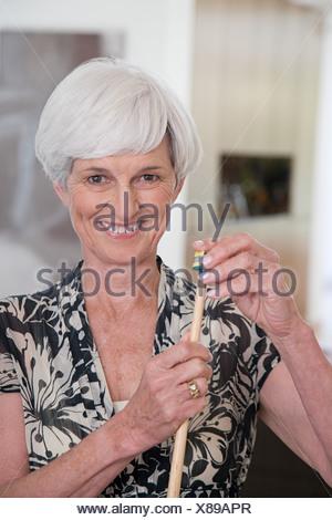 A senior woman holding a snooker cue - Stock Photo