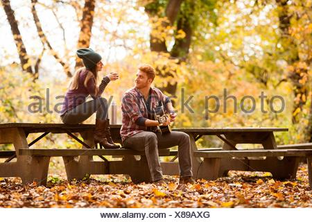 Young couple playing guitar on picnic benches in autumn forest - Stock Photo