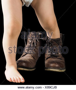 Toddler boy, leaving fathers brown over sized leather boots, isolated on black - Stock Photo