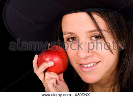 young girl with a witch hat holding a red apple - Stock Photo