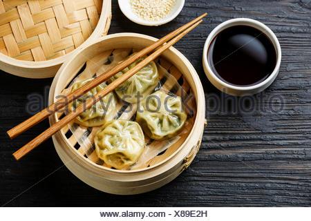 Steamed dumplings Dim Sum in bamboo steamer on black burned wooden background - Stock Photo