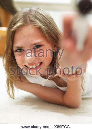 Girl smiling lying on her tummy - Stock Photo