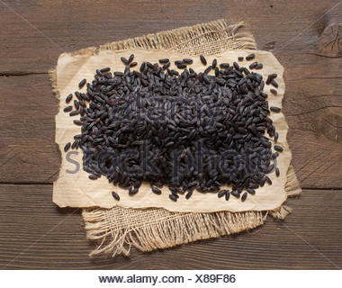 Black rice on a wooden table - Stock Photo