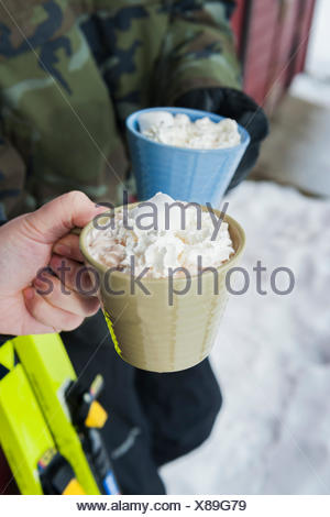 Sweden, Stockholm, Bjorkhagen, Hammarbybacken, Cropped view of man and woman holding mugs of hot chocolate with whipped cream - Stock Photo