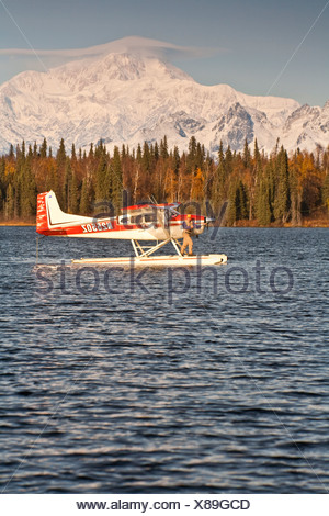 Flyfisherman fishing off of the float of a Cessna 185 floatplane on a lake with Mt. Mckinley and Alaska Range iin background - Stock Photo