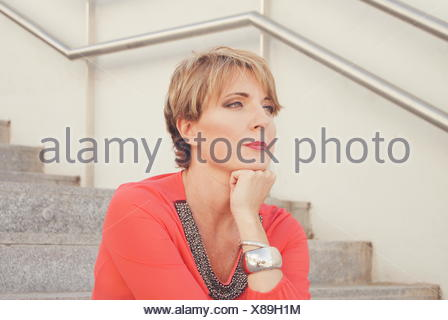 Woman sitting on stairs with head on her chin - Stock Photo
