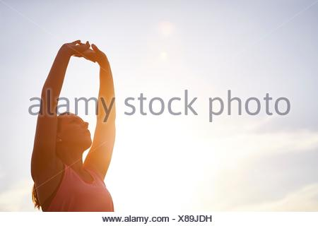 Young female runner stretching arms against sunlit sky - Stock Photo