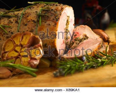 Sliced leg of stuffed lamb with garlic, rosemary and roast onion - Stock Photo