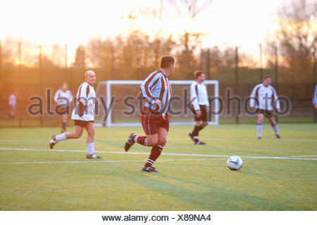 Football players running after ball - Stock Photo